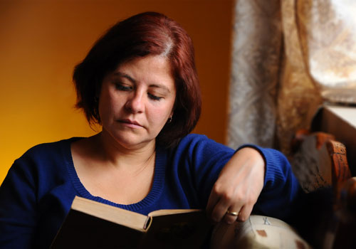 Image of a woman relaxed and reading by a window