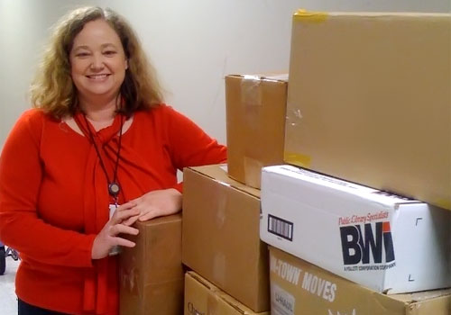 Image of employee standing by boxes of donated food